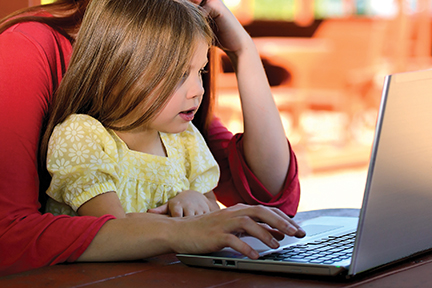 woman at laptop with young girl